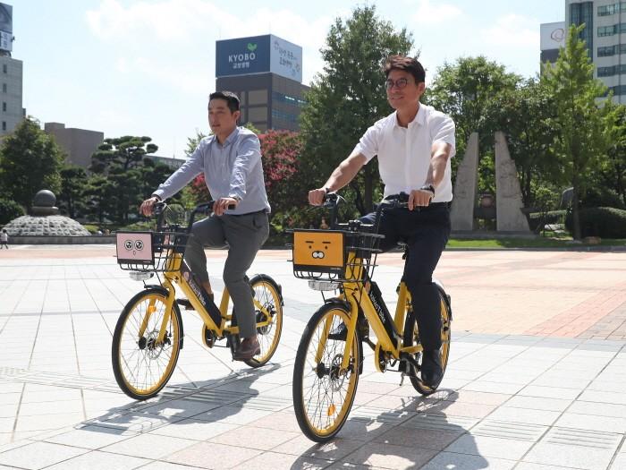 김춘수 울산시 교통건설국장(오른쪽)과 이성원 (주)카카오모빌리티 파트장이 울산시청 햇빛광장에서 '전기 공유자전거(카카오 T 바이크)'를 타고 시범 운행을 하고 있다(제공:News1)