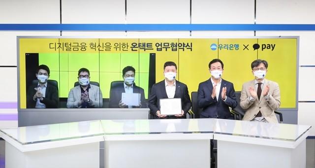 우리은행과 카카오페이가 10일 원격화상회의를 통해 업무협약을 체결한 후 기념 촬영을 하고 있다. 권광석 우리은행장(왼쪽 네번째)과 류영준 카카오페이 대표(세번째)가 협약서를 들어보이고 있다.