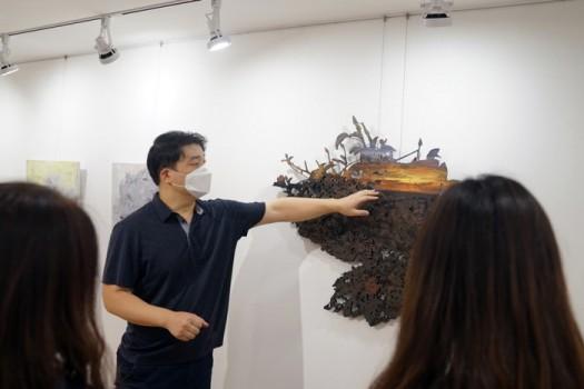 김민수 작가가 유디갤러리를 찾은 관객들에게 작품'낯익은 공허함2'를 설명하고 있다.