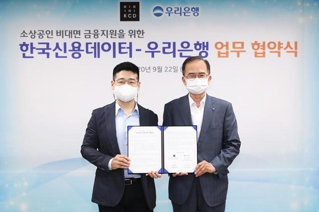 우리은행이 한국신용데이터와 소상공인 비대면 금융지원 업무협약을 맺었다. 서동립(오른쪽) 우리은행 중소기업그룹장과 김동호 한국신용데이터 대표가 기념 촬영을 하고 있다.