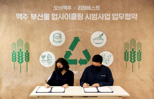 나탈리 보르헤스 오비맥주 구매/지속가능경영 부문 부사장(왼쪽)과 민명준 리하베스트 대표가 시범사업 업무협약에서 서명하고 있다.