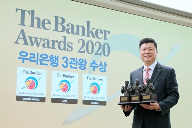 우리은행이 글로벌 금융전문지인 더 뱅커가 선정한 '글로벌 최우수 은행'과 함께 한국, 아시아 최우수 은행 등 3관왕의 영예를 안았다. 권광석 우리은행장이 기념 촬영을 하고 있다.