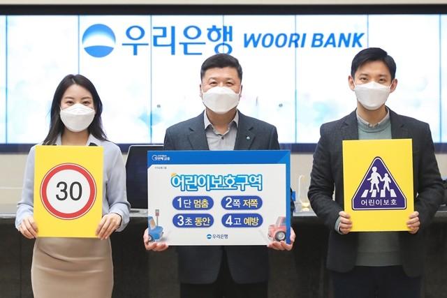 권광석 우리은행장(가운데)과 은행직원이 어린이 교통안전 릴레이 챌린지 참여 포스터를 들고 포즈를 취하고 있다.