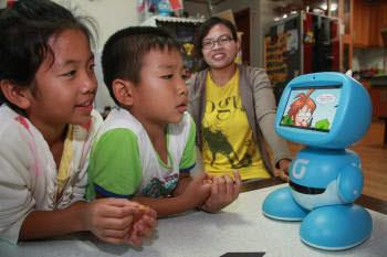 충북 충주시 대소원면 장성리 다문화 가정 자녀인 배신우 양(오른쪽 첫 번째)과 배재연 군 남매가 키봇2에 실린 교육용 만화를 보며 웃고 있다. 세 번째는 이들의 엄마 인도네시아 출신 도나 씨.