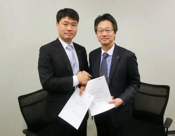 서형수 알서포트 대표와 나가타 NTT도코모 마케팅 부장이 지난 6일 도쿄 NTT도코모 본사에서 열린 업무 제휴식에서 향후 협약 내용이 담긴 서류를 검토한 후 악수하고 있다.