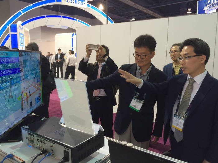 고삼석 방송통신위원회 상임위원(오른쪽 첫번째)이 박상규 카이미디어 대표로부터 실시간 HEVC 인코더에 관한 설명을 듣고 있다.