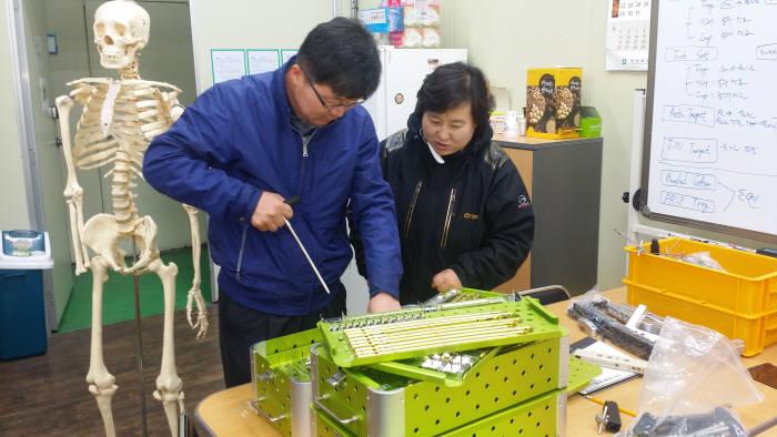 이경구 광주테크노파크 타이타늄센터장과 김선미 티디엠 대표가 생체의료용 임플란트 제품을 테스트하고 있다.