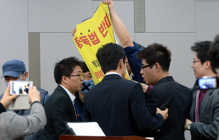 2012년 10월 국회에서 열린 '4대 중독예방관리제도 마련 공청회'에서 한 참석자가 중독법 반대 플래카드를 펼쳐보이자 관계자들이 나서 제지하고 있다. 박지호기자 jihopress@etnews.com