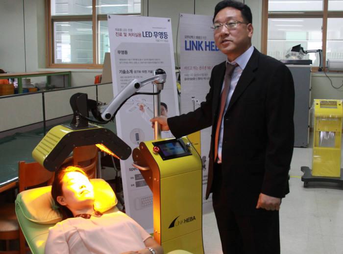 최용원 링크옵틱스 대표가 LED와 의료기술이 결합한 피부치료기 `링크헤바`를 시범 테스트하고 있다.