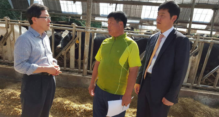 윤종록 정보통신산업진흥원장(맨 왼쪽)이 젖소에 스마트센서를 부착해 원유 생산 증대에 나선 청주의 한 축산 농가를 방문해 농장주(가운데)와 시스템을 개발한 회사 대표와 이야기를 나누고 있다.