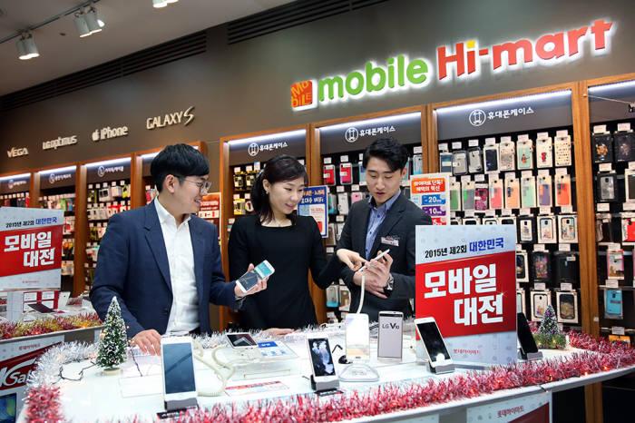 롯데하이마트 대치점 모바일 매장을 찾은 고객이 최신 스마트폰 상품에 관한 설명을 듣고 있다.