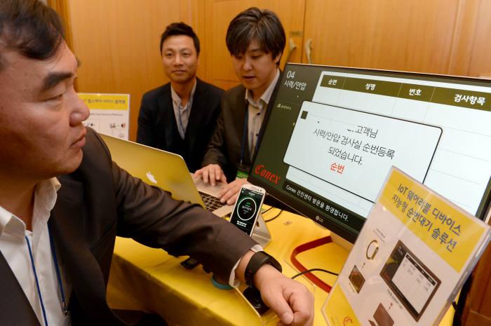 메디코넥스 부스에서 김태평 사장(왼쪽)이 IoT 웨어러블 디바이스 지능형 순번대기 솔루션을 시연하고 있다. 박지호기자 jihopress@etnews.com
