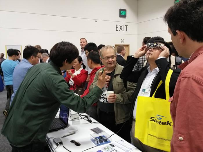 SID 디스플레이 위크 2016 전시장 내 국내 기업 라온텍 부스에서 관람객이 AR/VR 기기를 시연하고 있다.