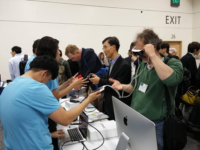 SID 디스플레이 위크 2016 전시장 내 국내 기업 테라클 부스에서 관람객이 AR/VR 기기를 시연하고 있다.