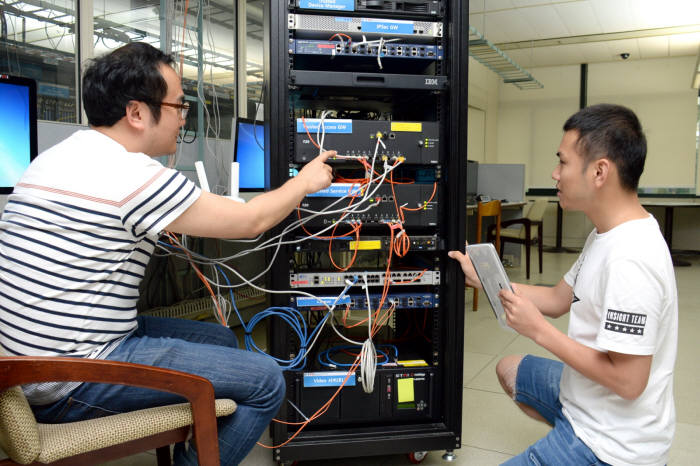 ETRI 연구진(왼쪽부터 명정호 선임연구원, 윤대근 연구원)이 단말에 탑재된 에이전트를 통해 가입자 및 단말 인증 과정을 거처 TIPN 네트워크에 접속, 와이파이 서비스를 확인하고 있다.