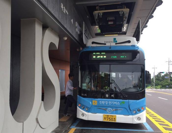13일 제주 서귀포시 망장포입구 정거장(시내 방면) 모습. 승객이 승하차 하는 동안 버스 위쪽에 자동로봇 시스템이 배터리를 교환하고 있다.