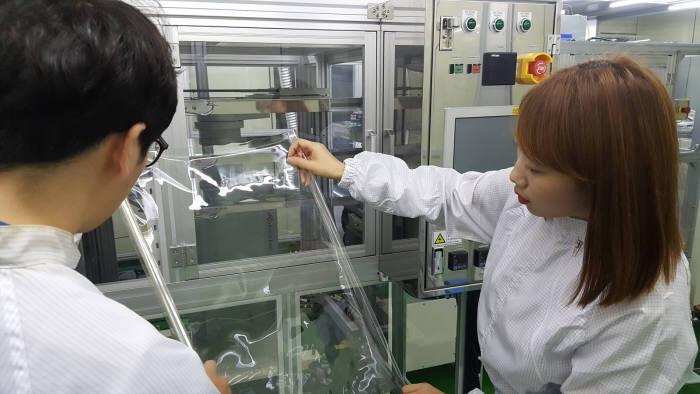 코오롱인더스트리 중앙기술원 연구원들이 투명한 폴리이미드(PI) 필름을 살펴보고 있다. (코오롱인더스트리 제공)