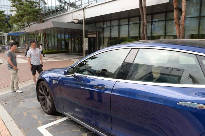지나던 회사원들이 세워져 있는 테슬라 전기차 모델S를 살펴보고 있다. (박지호 기자)