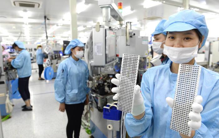 삼성전자 협력업체 ITM반도체 직원이 갤럭시노트7에 들어가는 보호칩을 생산하고 있다.<br />하노이(베트남)=박지호기자 jihopress@etnews.com
