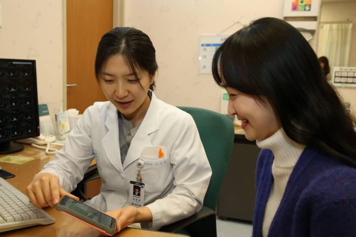 서울아산병원 의료진이 환자에게 만성질환 관리 앱 사용법을 설명하고 있다.