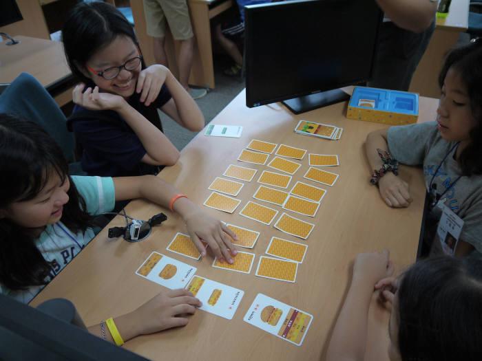 1회 드림업 SW교육에 참여한 학생들이 언플러그드 학습(컴퓨터없는 교육)으로 카드놀이를 즐기고 있다.