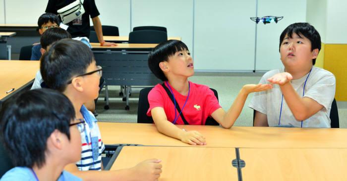 `1회 드림업 SW교육` 에 참여한 학생들이 드론을 띄워보고 있다.