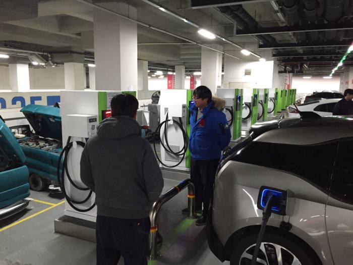 20일 오픈한 서울 잠실 롯데월드몰 지하주차장 충전소에서 전기차 이용자들이 충전하고 있다.