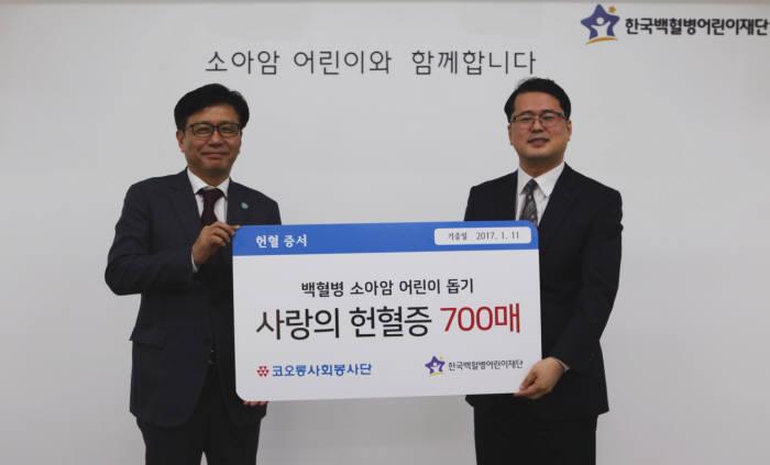 김승일 코오롱 CSR사무국 전무(왼쪽)가 서선원 한국백혈병어린이재단 사무처장에게 헌혈증을 전달하고 기념촬영하고 있다.