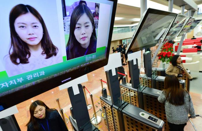정부청사관리본부가 서울, 과천, 세종, 대전 4대 청사에서 얼굴인식 시스템 시범운영을 시작했다. 정부서울청사 출입구에서 직원들이 얼굴인식 시스템을 이용해 출입하고 있다. 윤성혁기자 shyoon@etnews.com