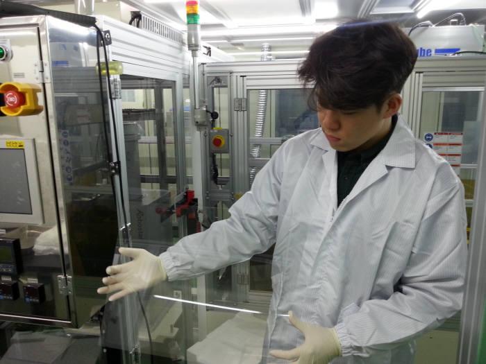 코오롱 직원이 WPM SFD 사업으로 개발한 투명 폴리이미드 바니시를 코팅해보고 있다. (사진=한국산업기술평가관리원)