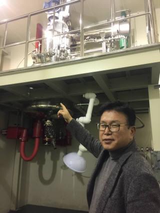 배병수 교수가 플렉시블 하드코팅 소재 양산 설비를 보여주고 있다.