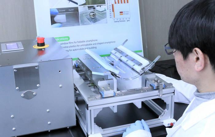 배병수 KAIST 신소재공학과 교수 연구팀은 폴더블 스마트폰 커버 필름 표면이 내구성을 구현하면서 접힐 수 있는 플렉시블 하드코팅 소재를 개발했다. 연구원이 하드코팅된 필름을 반복해 접는 등 내구성을 테스트하고 있다.