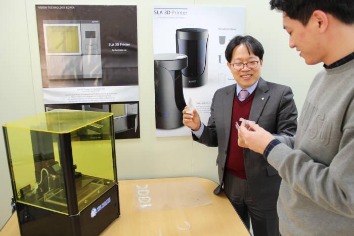 박지종 비즈텍코리아 대표(왼쪽)가 3D 프린터로 제작한 투명 치아 교정기를 살펴보고 있다.