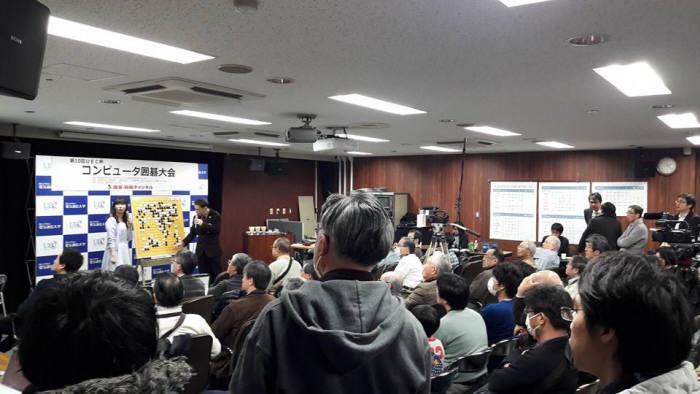 일본 도쿄에서 열린 UEC 주최 세계컴퓨터바둑대회에서 일본 딥젠고와 AQ 대국장에 참석자들이 설명을 듣고 있다. <사진=감동근 아주대 교수 제공>