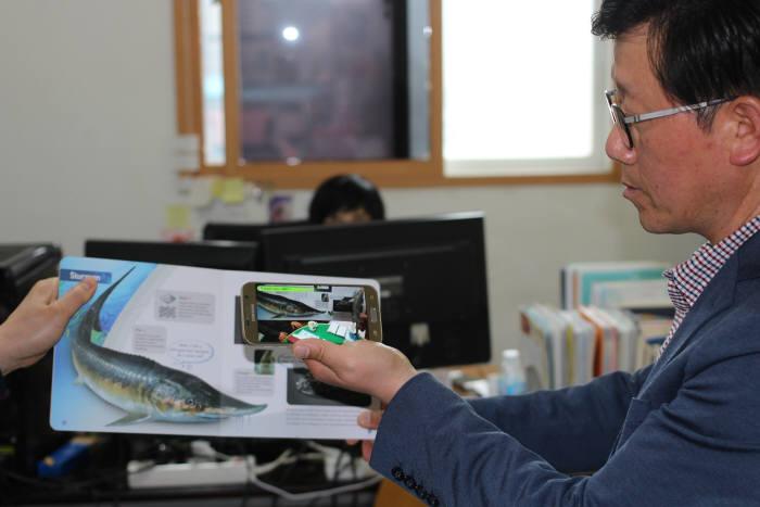 김상국 한울네오텍 부사장이 AR북을 스마트폰으로 시연해 보이고 있다.