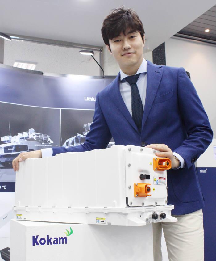 코캄이 국내 업계 최초로 출시한 전기차 전용 배터리팩 'XPAND'. 홍인관 코캄 이사가 포즈를 취하고 있다.
