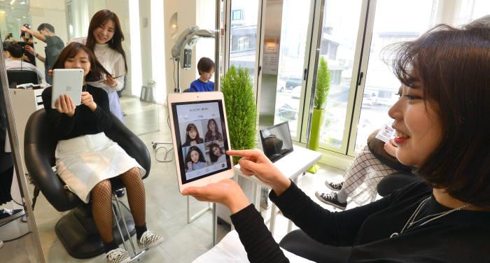 카카오톡에서 미용실과 고객을 이어주는 O2O서비스 '카카오 헤어샵'이 인기다.서울 서교동 유니크바이 헤어샵에서 고객이 '카카오 헤어샵' 앱을 통해 헤어스타일을 선택하고 있다. 김동욱기자 gphoto@etnews.com