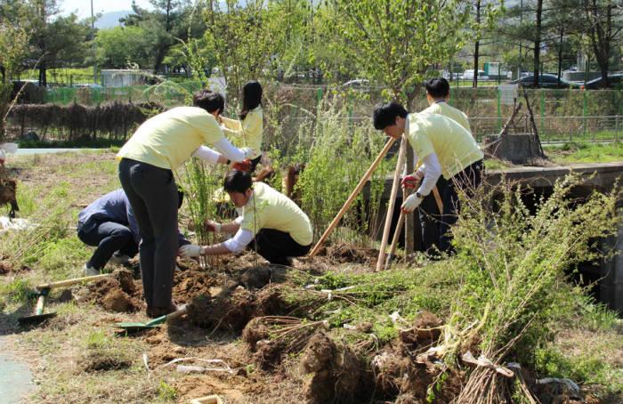 포시에스 임직원들이 나무심기 캠페인에 참여해 나무를 식수하고 있다.