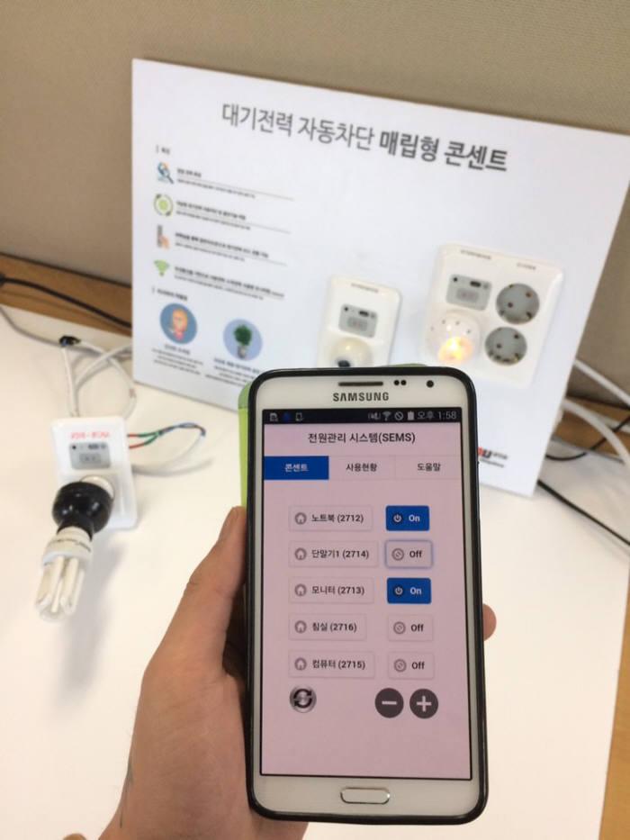 대기전력 차단 매립형 콘센트를 스마트폰 앱으로 제어하고 있는 장면