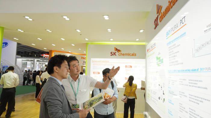 SK케미칼 직원이 차이나 프라스 2017에서 부스를 찾은 고객에게 PETG복합재에 대해 설명했다. [자료:SK이노베이션]