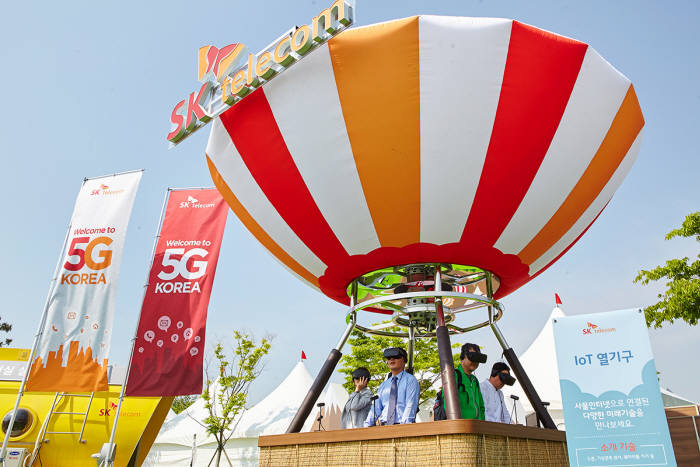 SK텔레콤은 18일부터 21일까지 인천 영종도 스카이72 골프앤리조트에서 'SK텔레콤 오픈'을 개최하고, 5G 시대의 실감형 미디어 서비스를 미리 경험할 수 있는 '5G 응용 서비스 체험 공간'을 운영한다고 밝혔다. 관람객들이 5G 열기구를 체험하고 있는 모습