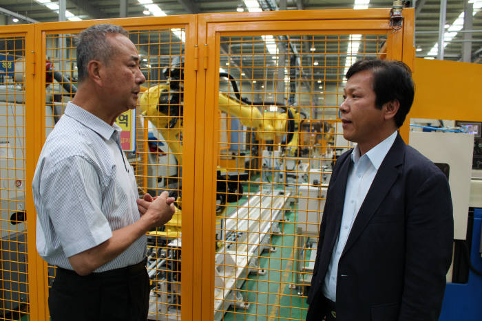 화신정공이 한국로봇산업진흥원의 로봇활용 중소제조 공정혁신 지원사업의 지원으로 최근 자동화 로봇을 도입했다. 사진은 김효근 대표(왼쪽)와 박기한 한국로봇산업진흥원장이 자동화로봇에 대해 의견을 나누고 있다.