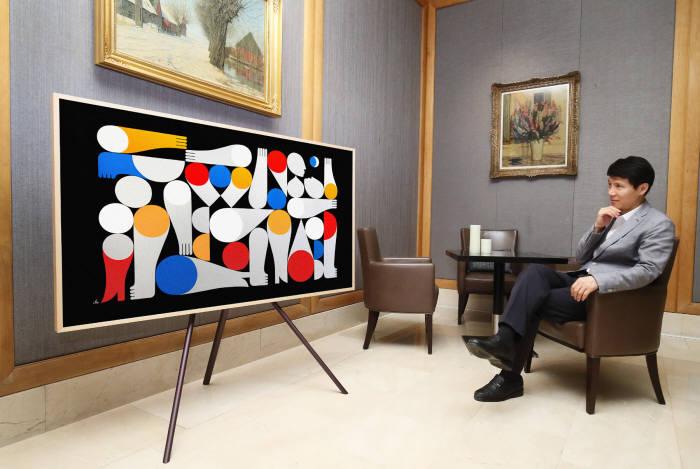 삼성전자 모델이 19일 JW 메리어트 호텔 서울의 1층 로비에 설치된 삼성전자 '더 프레임'을 보고 있다. '더 프레임'은 TV가 꺼져 있을 때에도 그림·사진 등의 예술 작품을 보여주는 '아트 모드'와 어떤 설치 공간과도 완벽한 조화를 이루는 '프레임 디자인'이 으로 일상 공간을 갤러리처럼 만들어준다.