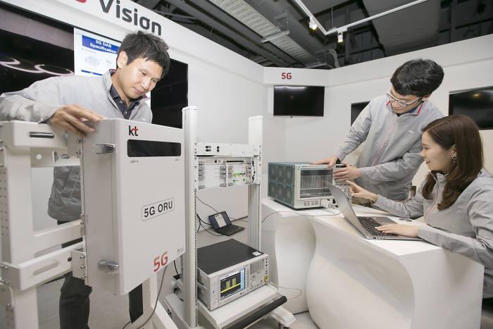KT 직원이 중소기업 협력사 직원들과 5G 중계기와 기지국을 연결해 5G 데이터를전송하는 테스트 진행하는 모습