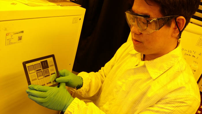 이현재 IBS 나노입자연구단 연구위원이 기판에 증착시킨 생체신호 측정 소자를 살펴보고 있다.