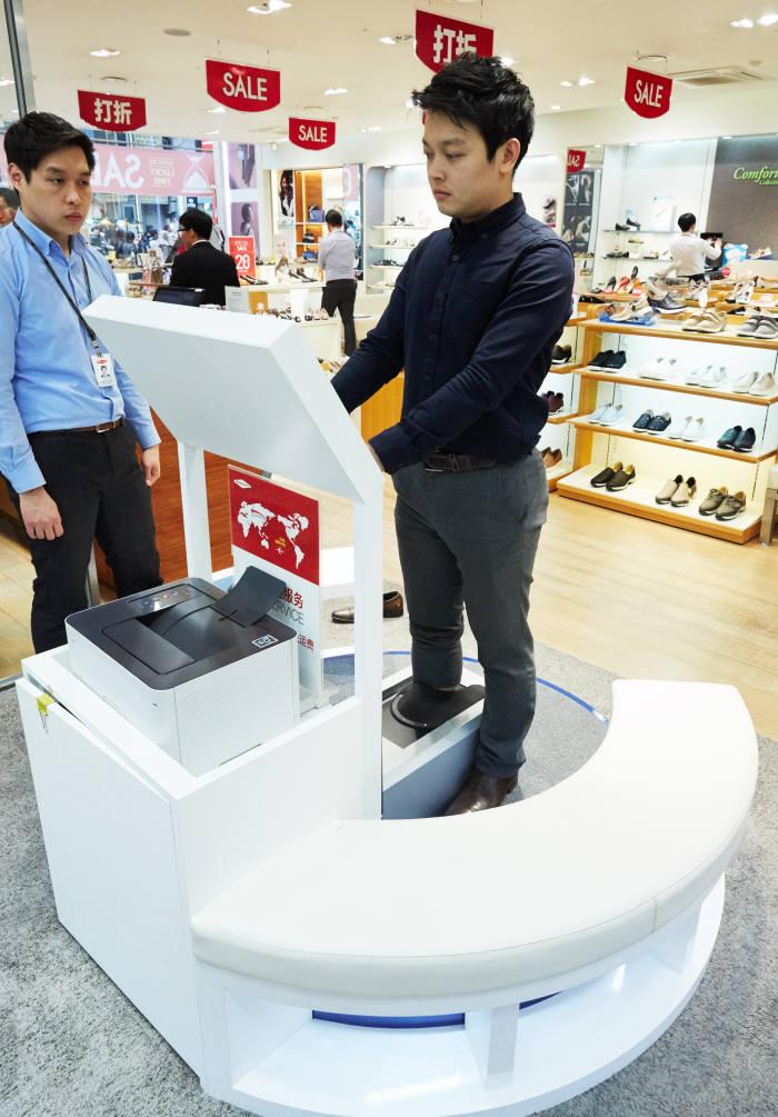 금강제화 명동점을 방문한 고객이 3D 풋스캐너를 이용하고 있다. (사진제공= 금강제화)>