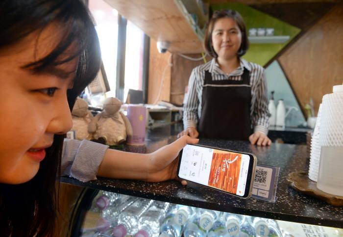 제주은행이 제주페이 출시를 앞두고 제주 전통 시장과 주요 관광지에서 모바일 지불결제 플랫폼 연동 작업을 시작했다. 동문시장 내 한 가맹점에서 고객이 근거리무선통신(NFC)를 활용한 모바일 결제 서비스를 하고 있다. 제주=박지호기자 jihopress@etnews.com