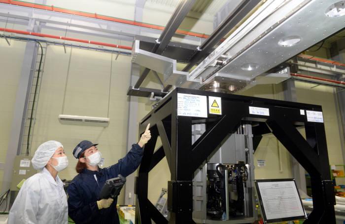 티이에스가 일본에 수출한 10세대 디스플레이용 진공 이송 로봇. 직원들이 경기도 오산 공장에서 수출을 앞둔 진공 이송 로봇을 살펴보고 있다. (사진=전자신문DB)