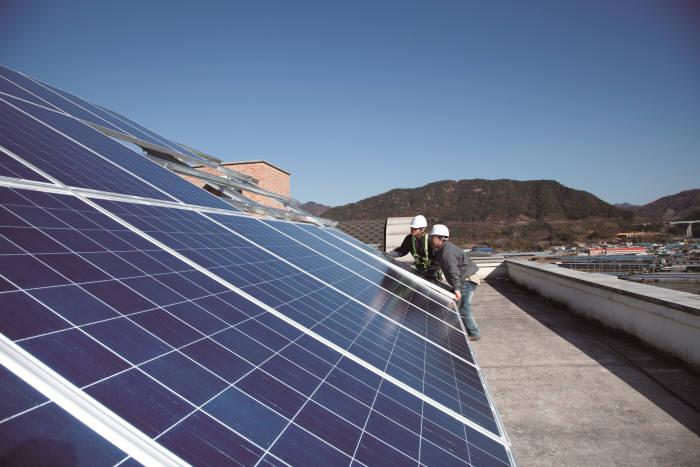 한화그룹 직원들이 복지시설 옥상에 태양광 발전설비를 설치하고 있다. [자료:한화그룹]