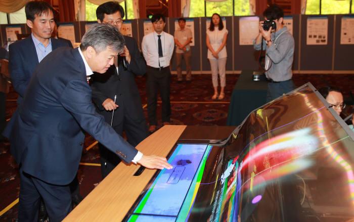 이인호 산업통상자원부 1차관(맨 왼쪽)이 지난 6월 22일 서울 송파구 올림픽파크텔에서 열린 '투명 플렉시블디스플레이 R&D 성과 보고회'에서 스마트 데스크, AR space 등 미래형 디스플레이 제품 전시장을 둘러보고 있다. (사진=산업통상자원부)